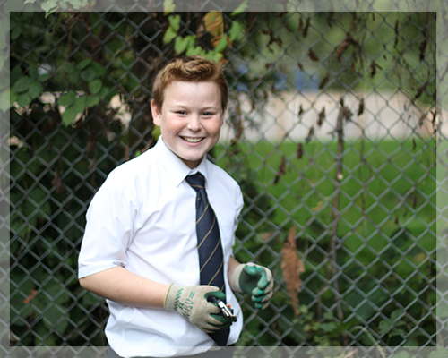 Student wearing gardening gloves in the school garden.